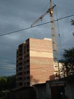 На картинке изображён недостроенный дом и строительный кран. Юрист по недвижимости