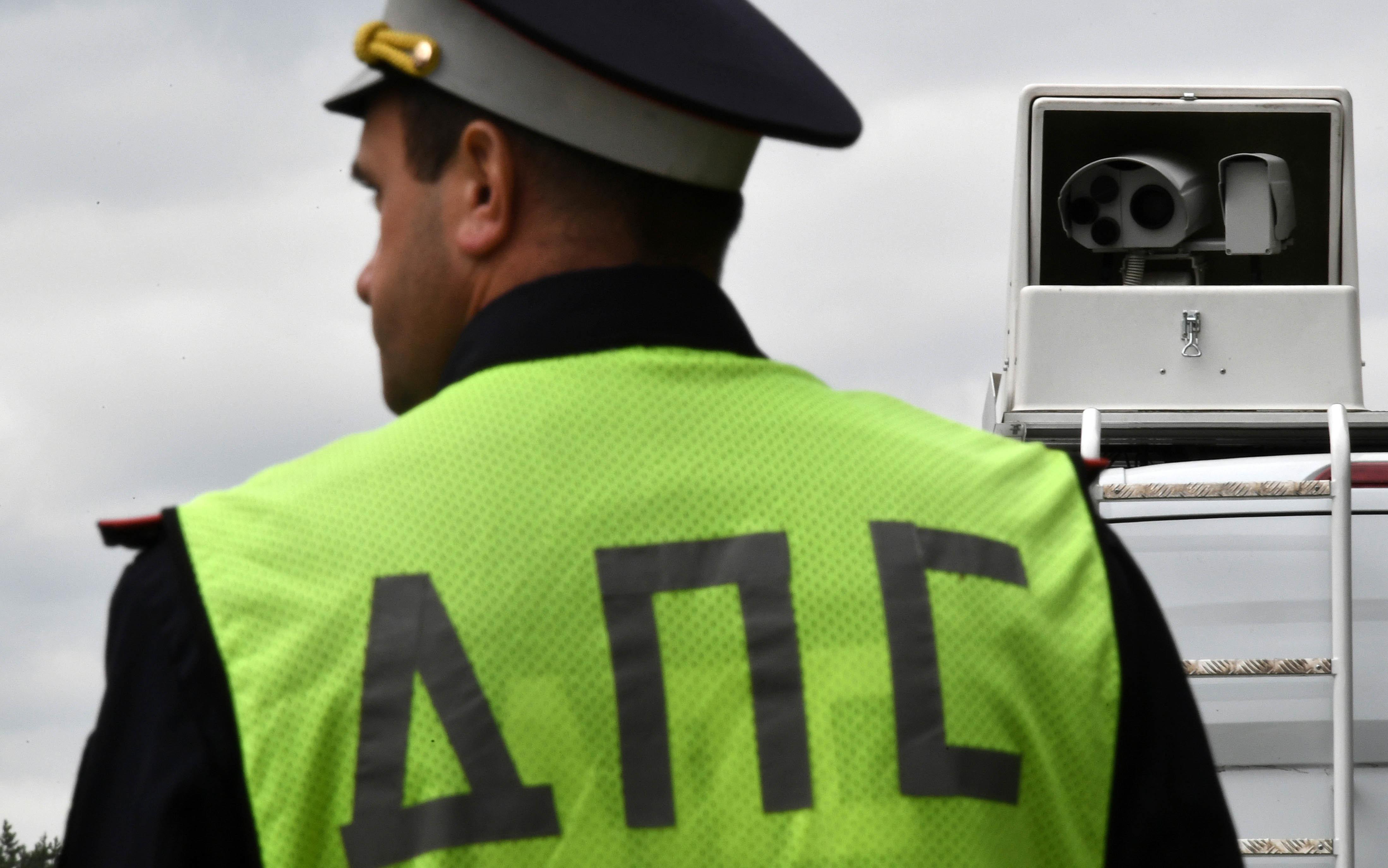 На картинке изображено Гаишник в форме спиной рядом с видеокамерой. ГИБДД начала кампанию по борьбе с превышением скорости на 19 км в час